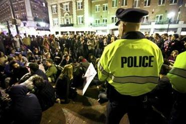 Cambridge Police officers kept watch over group of Occupy protesters outside the gates at Harvard University last night.