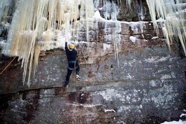 "for Travel - 29icefest - A climber ascending a ""mixed climb."" Mixed climbing includes not only using the tools to climb ice, but also thin rock features like cracks that are too small for a climber's fingers or hands to grip. (Dominic Casserly)"