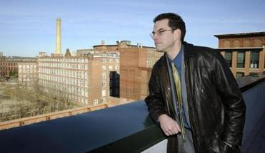 for Globe North - 05nomills - Lowell, MA - 12/20/2011 - Assistant City Manager Adam Baacke (cq) looks out from a roof deck at Appleton Mill Lofts onto other mills that have also been rehabbed. (Mark Wilson for The Boston Globe)