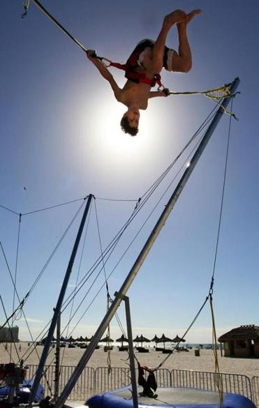Tyler Bernstein, 13, of St. Louis, celebrates the first day of winter by performing aerial somersaults on the beach at Marco Island, Fla.