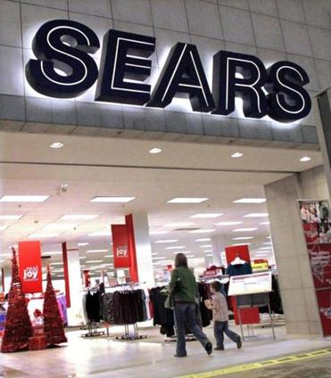 In this Nov. 15, 2011 photo, customers enter a Sears store, in Springfield, Ill. Sears Holdings Corp.'s third-quarter loss widened, dragged down by weakness in Canada, declining consumer electronics sales and softer clothing sales at its Kmart stores. (AP Photo/Seth Perlman)
