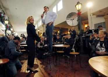 Mitt Romney stood atop a chair, steadied by his wife, Ann, to address a crowd at Music Man Square in Mason City, Iowa. He has tried to loosen up and bond with voters.