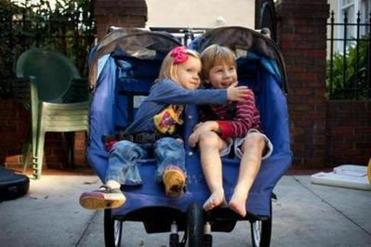 Grace Gilmore and her brother, Brooks Lennon, played together in their stroller while waiting to be taken for a walk around their neighborhood in Tampa.