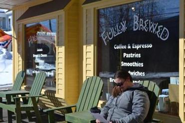 Woodstock, N.H., resident Stacey LaPierre soaks up sun rays in front of Half-Baked & Fully Brewed, a cafe and sandwich shop that is popular with both tourists and locals.