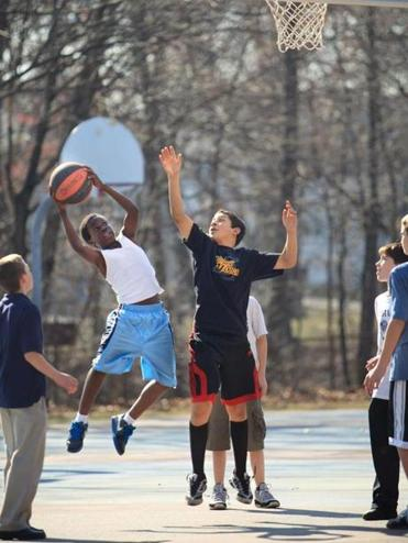 Iragi Nkera went in for a layup against Quentin Harris  during a lively game of basketball at Dugger Park in Medford.
