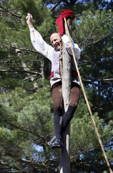 Roy Kring of the Bedford Minutemen gestured in triumph after climbing the pole.