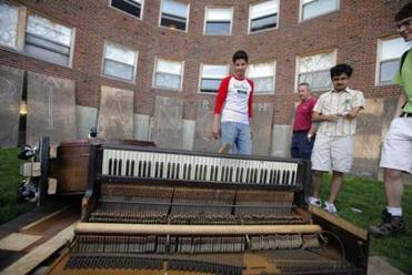 Student Aziz Albahar checked the damage after a baby grand was dropped onto another piano in 2008.