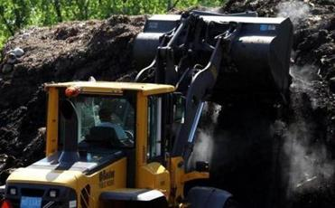 A front loader turned a pile of compost at the storage site in Mattapan. Since 1995, the amount of compostable material in Boston increased from 638 tons to more than 11,000 tons last year.