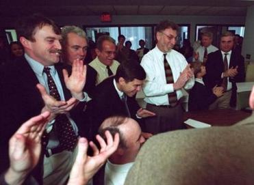 Boston Globe staffers reacted as news of the paper's Pulitzer Prize for Public Service was received over the newswires in 2003. Looking on were (left to right): Matthew Carroll, Kevin Cullen, Stephen Kurkjian, Michael Rezendes, and editor Martin Baron.