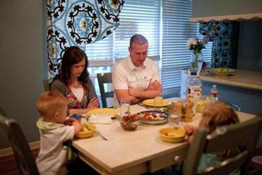 The Hamblin family prays before their evening meal. Bryan and Jenny Hamblin, who are Mormons, both voted for Obama in 2008, but are undecided now.
