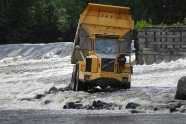 A dump truck was used to build a road into the Penobscot River on the Bradley-Old Town line for hauling away the Great Works Dam after it is dismantled.