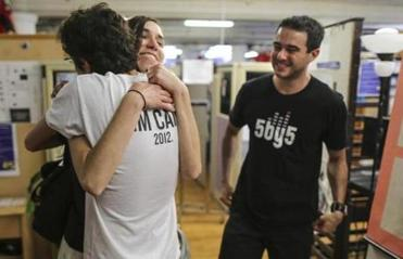 06/15/2012 BOSTON, MA L-R Julianna Morris (cq) hugs Conrado Santos (cq) 24 (Brazil), as Denis Lemos (cq) 26 (Brazil) stands beside them during an event held at the Student Immigration Movement's (cq) office in Boston. The Obama (cq) administration announced it will grant work permits to young illegal immigrants who came to the US as children and have led law-abiding lives. (Aram Boghosian for The Boston Globe)