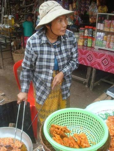 A woman fried cakes of whole shrimp and rice flour in the village of Kampong Phluk, Cambodia.