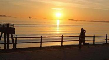 A jogger and the sunrise from Castle Island..