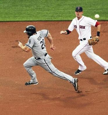 Kevin Youkilis of the White Sox races past Red Sox third baseman Will Middlebrooks after he noticed no one was covering third on an infield shift at Fenway Park on July 17, 2012.