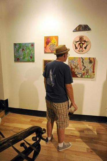 Lowell resident Mike Flynn checks out some art at last month's opening of Zeitgeist Gallery, an art cooperative on Market Street that adds to the city's downtown art scene.