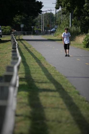 Milford and Franklin officials hope more residents will follow the example of Jaider Lopes, 14, as he walks along the Upper Charles Trail in Milford.