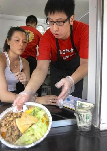 Jenny Giang and Ian So, serve meals from the new Chicken & Rice Guys food truck.