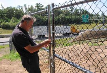 Carver official Jack Hunter has to get past a locked gate to visit the town's solar-panel project alongside Route 44.