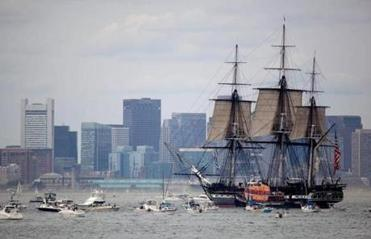 The USS Constitution passed through Boston Harbor with open sails to commemorate its victory over a British frigate in 1812.
