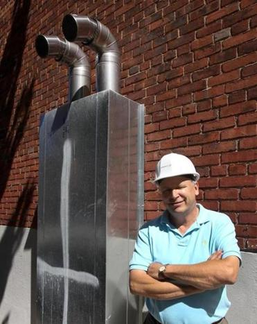 Ameresco's Steve Turner next to an exhaust outlet at a Boston Housing Authority site. Ameresco has been outfitting BHA apartments with new lighting and water systems.