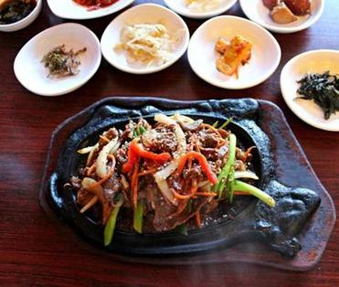 Beef bulgogi in a sizzling platter surrounded by side dishes.