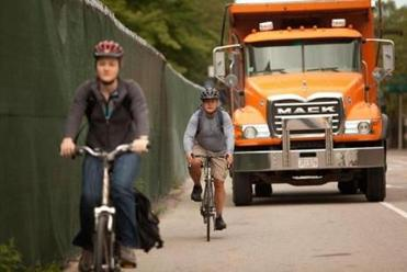 Globe movie critic Ty Burr shares the road with another cyclist and a truck along Longwood Avenue, one of the routes he takes from his Newton home to the paper's offices in Dorchester.