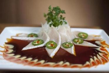 Sashimi topped with chili slices and shaved daikon.