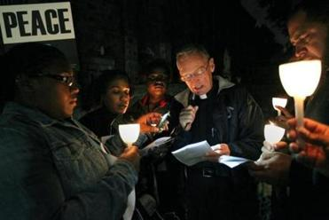 "Father Richard ""Doc"" Conway and Susan Young (second from left) read a prayer in front of St. Peter Church during a peace march on an October night ."