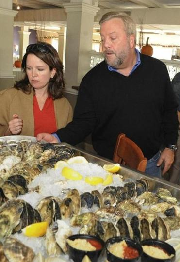 Karen Scalia, founder and owner of Salem Food Tours, left, talked with George Carey, founder, proprietor of Finz Seafood & Grill in Salem, MA