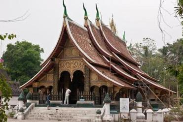 "Wat Xieng Thong, or ""Temple of the Golden City,"" is in its fifth century, located in a garden on the bank of the Mekong River."