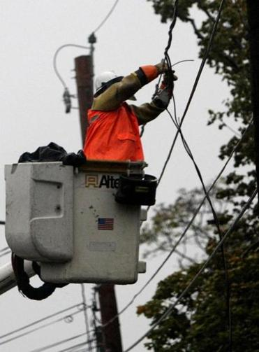 An electrical worker secured wires knocked down by falling branches in Watertown.