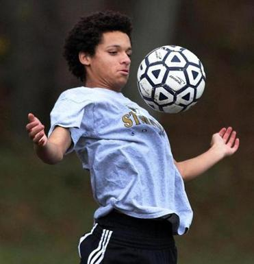 Alexander Alleyne of the St. Mary's of Lynn boy's soccer team keeps his eye on the ball at a Halloween practice.