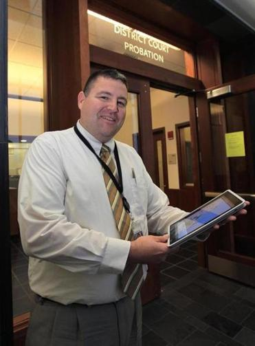 Plymouth District Court Probation Officer James Polin, cq, uses an iPad to help him with his probation work