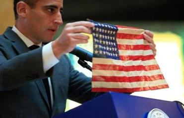 Boston City Councillor Michael P. Ross held up a small American flag given to his father, Stephan Ross, by Sattler.