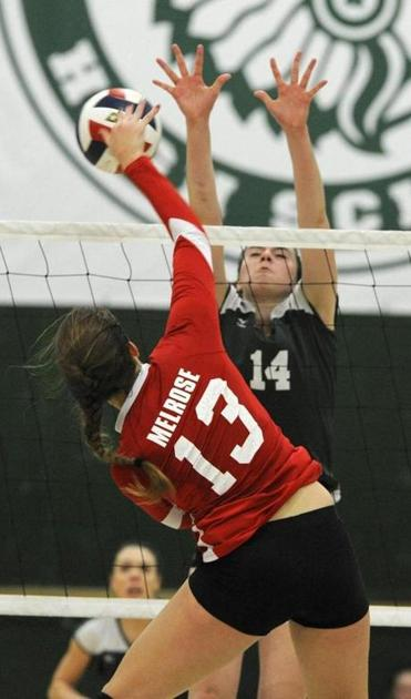 Canton's Julia Murphy goes high above the net to block Melrose's Sarah McGowan's shot, but the Red Raiders came out on top.