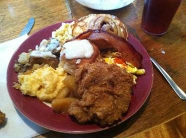 A heaping breakfast plate with skillet fried chicken.