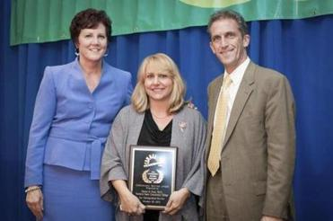 Dawna M. Perez (center) receives the Community Service Award from Karen Frederick (left), executive director of Community Teamwork Inc., and Lane Glenn, president of Northern Essex Community College.