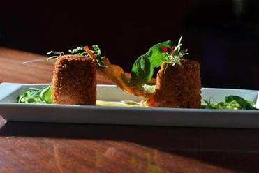 The confit croquette appetizer of duck and potato with spicy aioli, duck skin, and pepitas at Lord Hobo in Cambridge.
