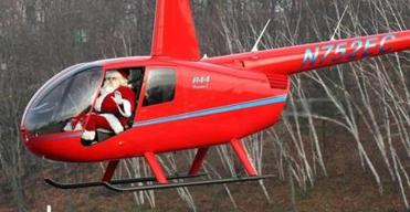 Santa Claus flies over the Maynard Christmas parade with the passenger door open so the children can see him wave.