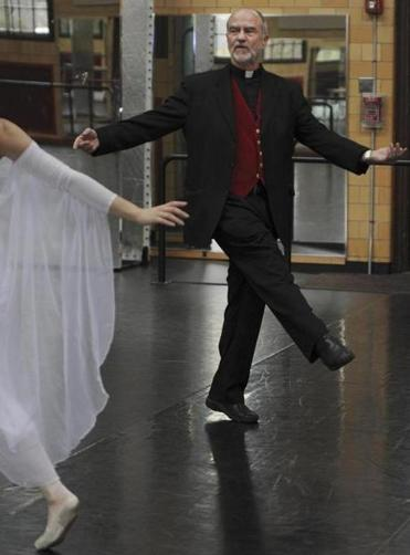 "At Boston College, the Rev. Robert VerEecke rehearses ""Christmas Reflections"" with dancers in a gym."