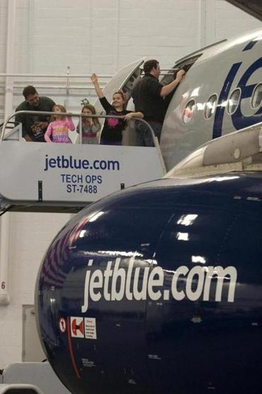 The family of a JetBlue Airways employee waits to board an airplane during a celebration marking the airline's move to Hangar 8 at Logan International Airport in Boston Monday.