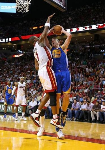 Golden State's David Lee keeps his eye on the prize despite tight defense from Chris Bosh.
