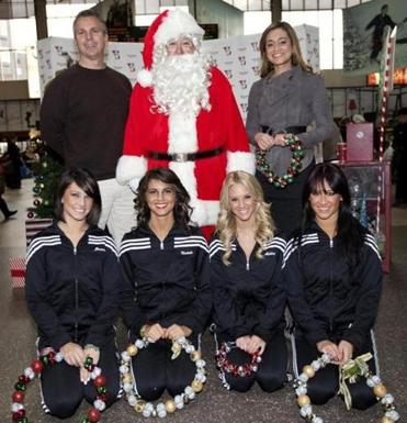 Kevin Lemanowicz and Sorboni Banerjee of Fox 25 News joined Boston Celtics dancers Jessica, Nichole, Ashley, and Amanda in giving Globe Santa a hand at South Station.