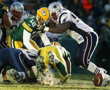 Patriots defensive lineman Ty Warren roughed up Packers backup quarterback Aaron Rodgers as players sought a loose ball.