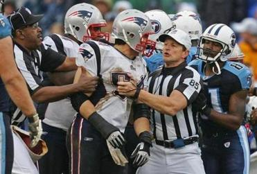 Referee Ed Hochuli restrained Tedy Bruschi after a questionable play on which Rodney Harrison was injured.