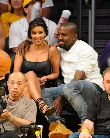 Kim Kardashian and Kanye West (shown at a Lakers game in May) have announced that they are expecting a child.
