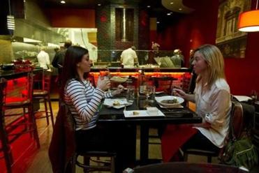Carrie Darman of Belmont (left) and Morgan Vokey of Waltham enjoy a meal at Charcoal Guido's.