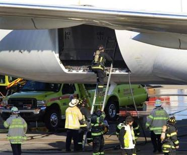 Firefighters checked out the area where a small fire broke out on a Boeing 787 Dreamliner at Logan Airport Monday. The fire knocked out Boston's only nonstop flight to Asia.