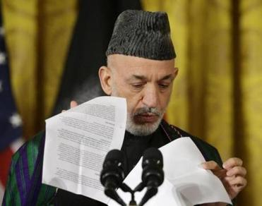 Afghan President Hamid Karzai looked through his notes.